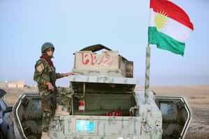 A peshmerga fighter stands on a military vehicle