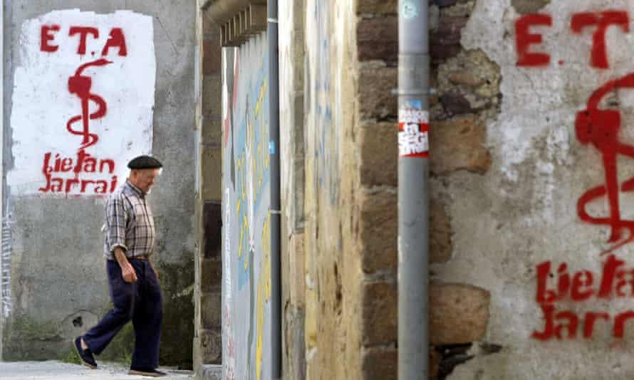An old man walks past graffiti depicting the logo of Basque separatist group Eta in Goizueta