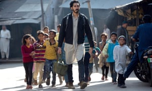 Man walking in street in Indian sub-continent followed by a gaggle of very young children.