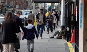 Pedestrians walk in the Tenderloin district of San Francisco, known for having many homeless people.