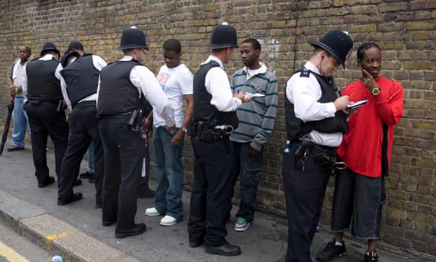 Police stop and search black youths at the entrance to the Notting Hill Carnival.