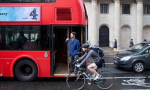 A red bus goes past the Bank of England in the City of London