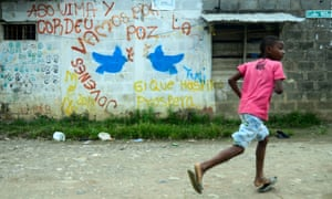 A boy runs near a mural reading 'Youngsters let's go for peace' in Apartado, Colombia, in June 2016.