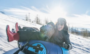 Mother and son tubing downhill.