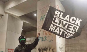 A protester holds up a Black Lives Matter sign in front of the Federal Courthouse in Portland on Saturday night