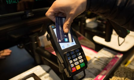 A customer uses a credit card to make a contactless payment.