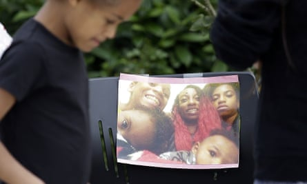 A girl walks past a memorial outside the apartment where Charleena Lyles was shot and killed by police on Monday.