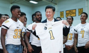 The Chinese president, Xi Jinping, is presented with a sports shirt by students during his visit to the Lincoln high school in Tacoma, Washington state, earlier this week.