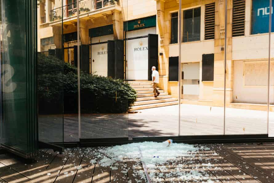 A man walks past the chattered window fronts of a recently closed bar in the commercial centre of Beirut, on 16 July, 2020.