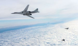 Two RAF Typhoon fighters escort a Russian TU-160 bomber