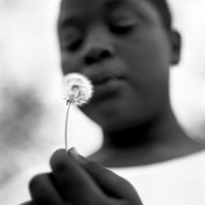 A young boy makes a wish as he blows the seeds of a dandelion at his home in Duncan, April 2011