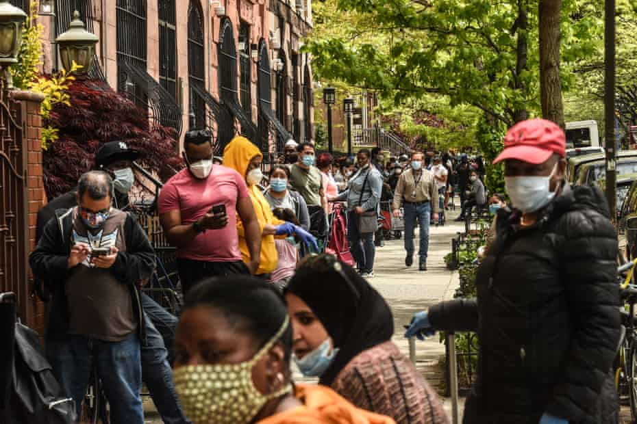 People wait to receive a food bank donation at the Barclays Center sports arena in New York City on 15 May.