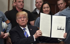 President Donald Trump holds up the proclamation on aluminum.