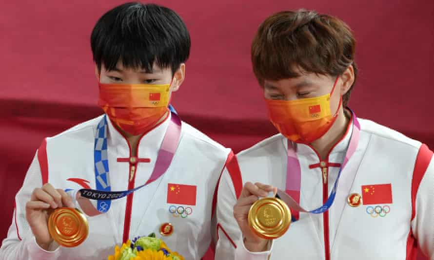 Bao Shanju and Zhong Tianshi wearing badges of the late Mao Zedong at the women's team sprint medal ceremony.