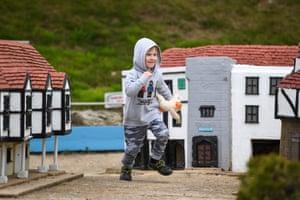 Boy runs past tiny houses