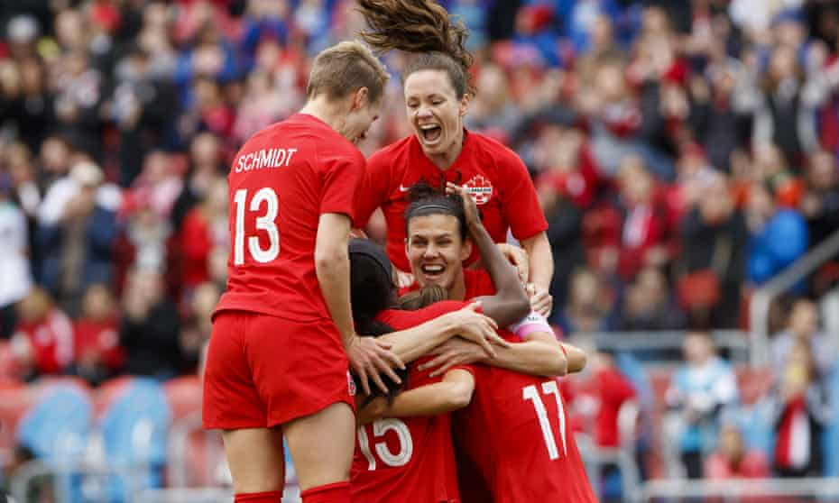 Canada captain Christine Sinclair, is mobbed by her teammates after scoring against Mexico in Toronto