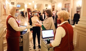 Staff in red and white uniforms and masks check tickets in the foyer