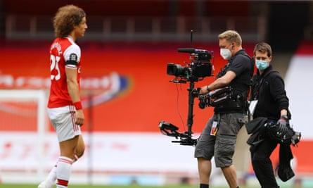 Arsenal's David Luiz walks past camera operators who are wearing masks during a Premier League match.