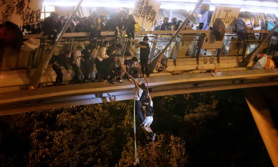 Anti-goverment protesters trapped inside Hong Kong Polytechnic University abseil on to a highway.