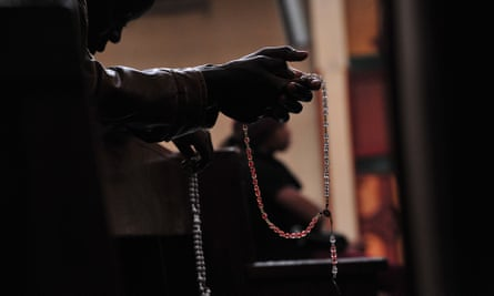 Person praying with a rosary.