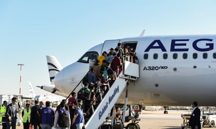 Unaccompanied children board a plane in Athens on their way to shelters in Germany
