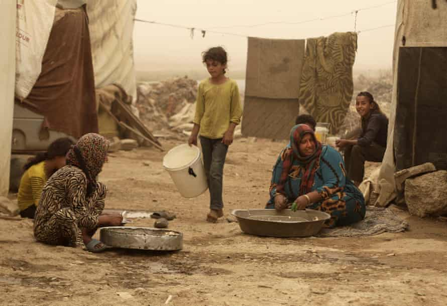 Syrian refugees outside their tents during a sandstorm, in a camp in Lebanon's Bekaa Valley.