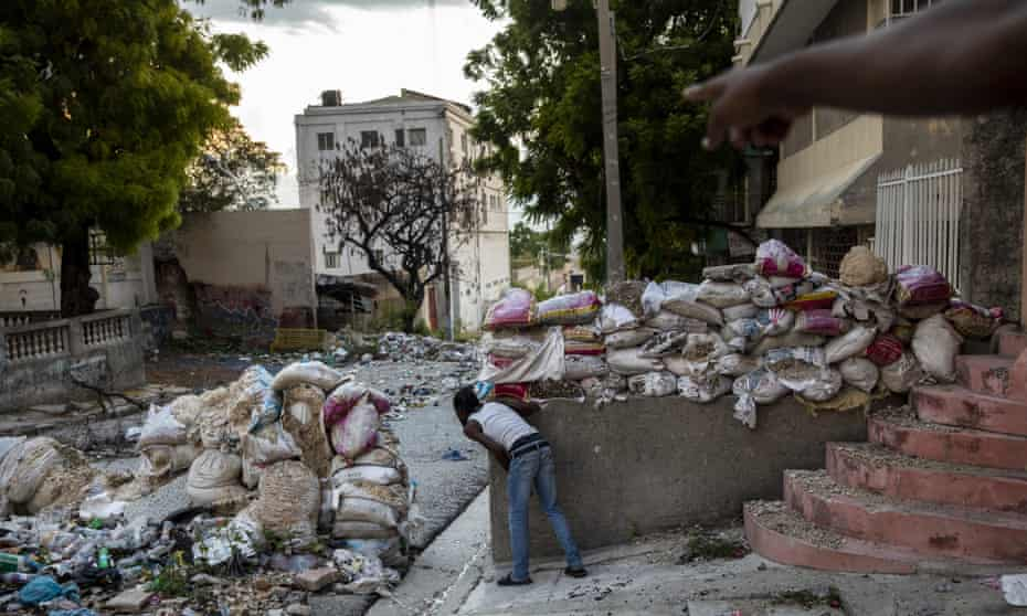 A lookout keeps an eye on rival gangsters in downtown Port-au-Prince, Haiti, in September. At least 165 gangs – many with tacit political backing and support – operate in the country.