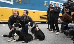 Chasten Buttigieg, left, along with husband Pete and a supporter's dogs, at a 2020 campaign stop in Claremont, New Hampshire, last month.