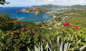 Nelson's Dockyard and English Harbour in Antigua, with azure sea beyond, seen in the distance from Shirley Heights in Antigua