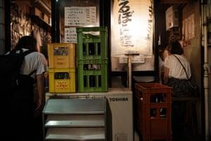 A woman peeks into a packed izakaya restaurant, a type of Japanese pub