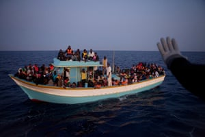 A boat coming from Libya is intercepted by the coastguard, who escort it to the port where police and volunteers are waiting for the 158 people on board.