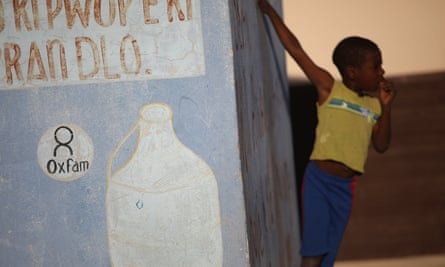 A boy stands next to an Oxfam sign on a kiosk on the outskirts of Port-au-Prince, Haiti