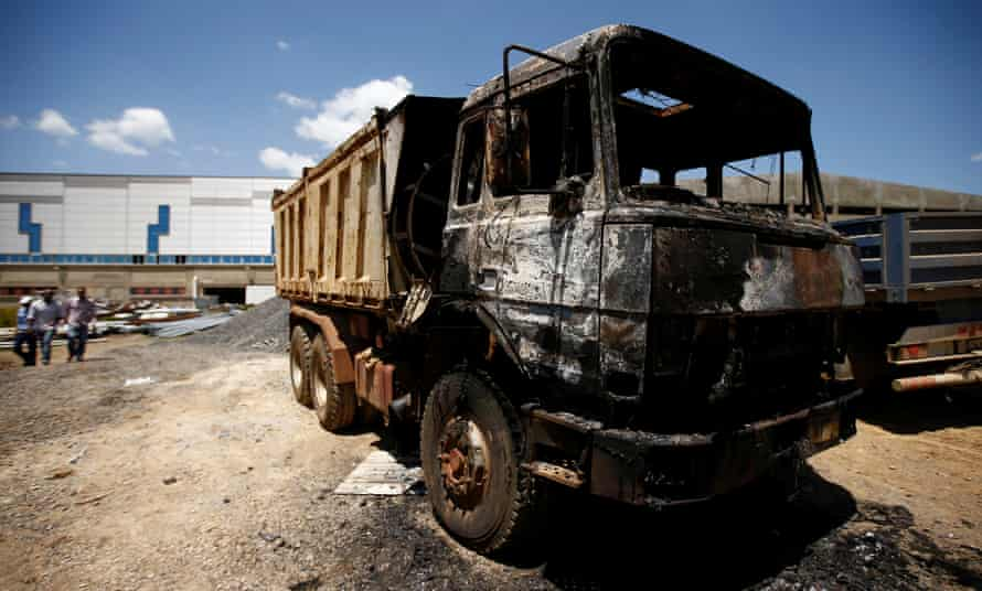 People walk near a torched truck damaged by protests in the town of Sebeta, Oromia region, Ethiopia