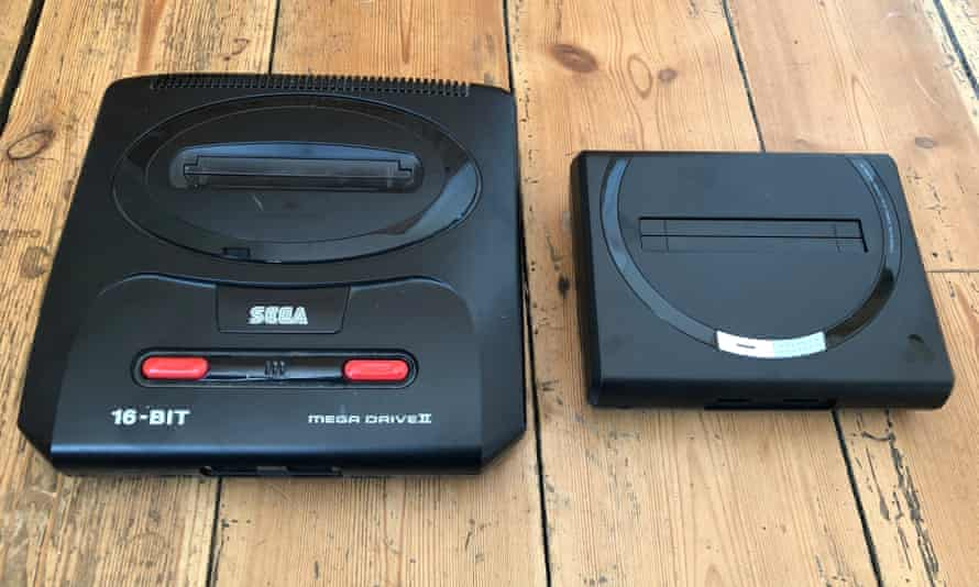 The Analogue Sg photographed next to an original Mega Drive II. The new machine replicates the circular motif around the cartridge port and retrains the headset port in the front