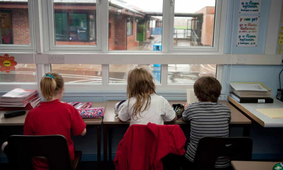 Rear view of three Primary school children sitting at their desk