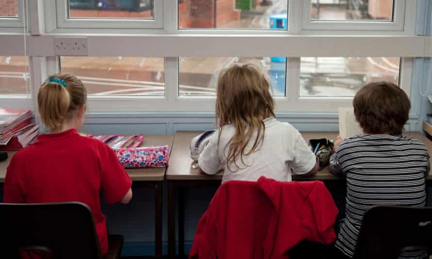 Primary school children sitting at a desk.