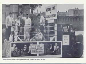 Black and white photo; a truck has been converted into a carnival float with a boxing ring on the back.  There are two boxers, one on the floor, two towel men, and a referee holding one boxer's gloved hand high in victory.  Signs on the float tell us this is Nosmo King vs. Lung Cancer, and that Lung cancer kills someone every 20 minutes.