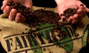 hands holding coffee beans over sack with fairtrade logo