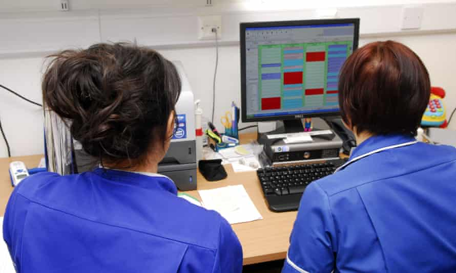 Healthcare workers look at a computer screen
