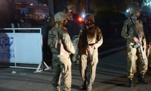 Pakistani troops guard a cordon around the site of suicide bombing in Lahore that left more than 70 people dead.