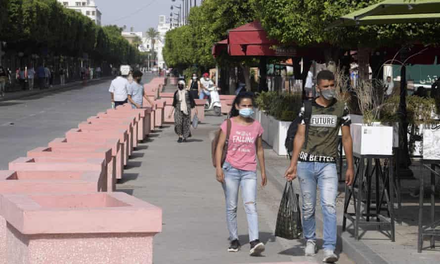 Tunisians walk along Avenue Habib Bourguiba in Tunis on Tuesday
