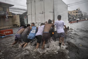 Lipa, Philippines. Residents push a stalled van off a flooded road during the onslaught of Typhoon Kammuri in Batangas province. Tens of thousands of people have been evacuated