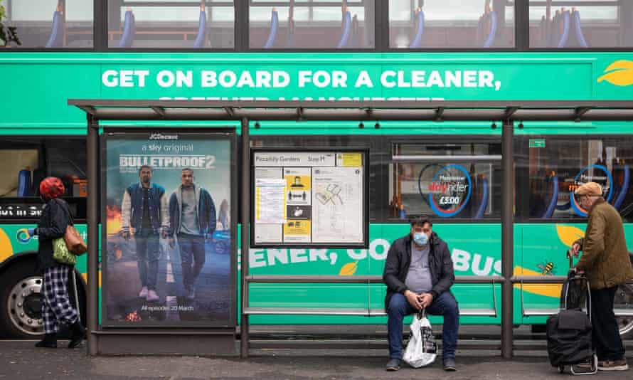 A public transport user in Manchester wears a mask as he waits for a bus.