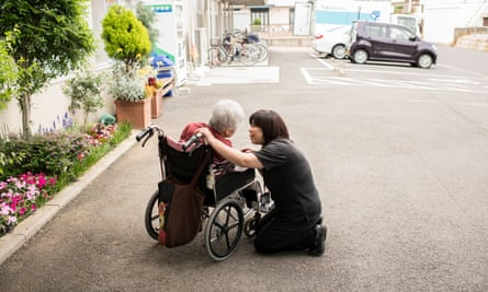 a member of staff at a dementia day centre in japan speaks to a customer