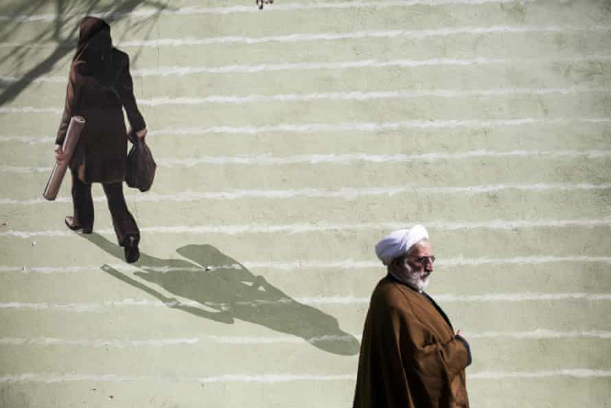 An Iranian clergyman walks past a mural depicting a woman in downtown Tehran.