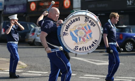 Orange Order members march past Ardoyne shops on the Crumlin Road in Belfast.
