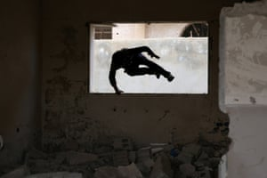 Parkour coach Ibrahim al-Kadiri, 19, demonstrates his parkour skills amid damage in the rebel-held city of Inkhil, west of Deraa, Syria, February 4, 2017. Led by Ibrahim, the team trains on quiet days.