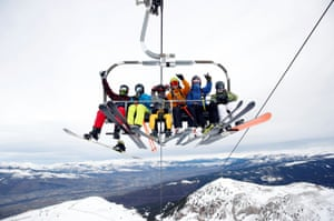 Skiers and snowboarders on a chairlift at a reopened ski resort in Masella, Spain