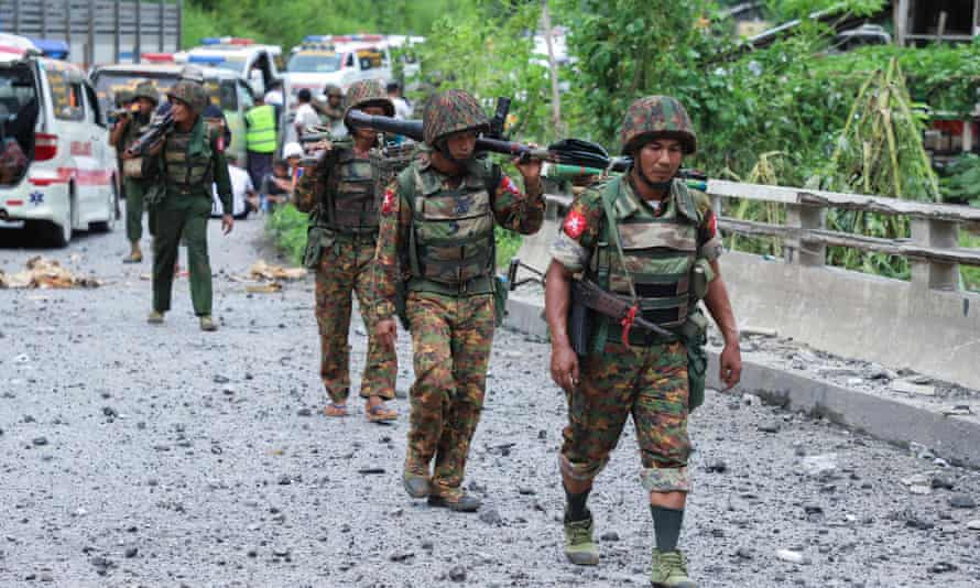 Myanmar troops cross a bomb damaged bridge in Shan State on Thursday after it was attacked by ethnic rebel groups in fighting that has killed at least 14.