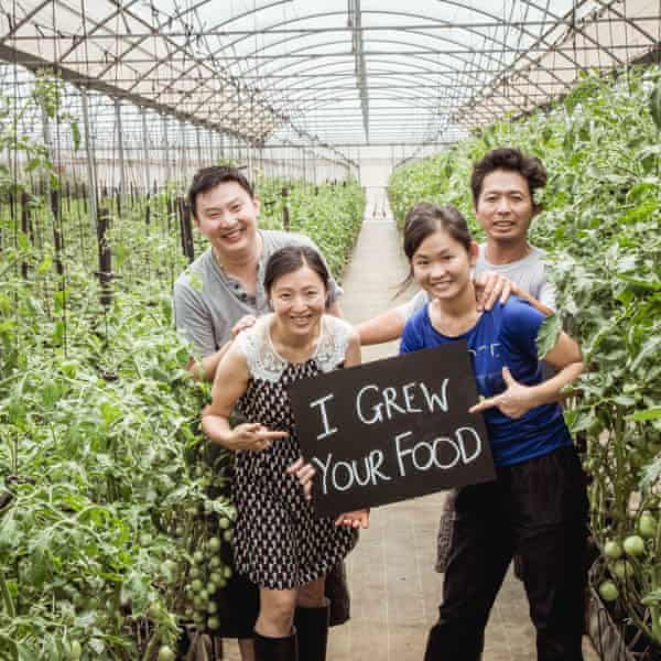 The Golden Fields team on their farm, holding a sign that says 'I grew your food'.
